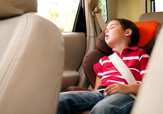 Litle boy sleeps in safe chair in car