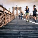 people jogging on a bridge trying to reduce their body mass index